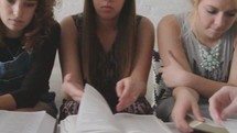 Teen girls turning the pages of their Bibles during a Bible study group.