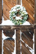 snow on a wreath on wood barn doors