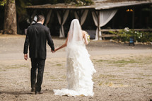 bride and groom walking hand in hand outdoors to their wedding reception