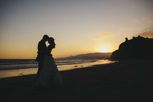 bride and groom standing on a beach at sunset