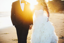torso of a bride and groom holding hands walking on a beach