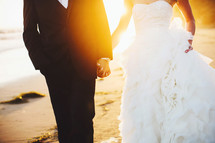 bride and groom holding hands walking on a beach