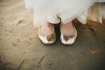 woman in ballet flats standing in the sand