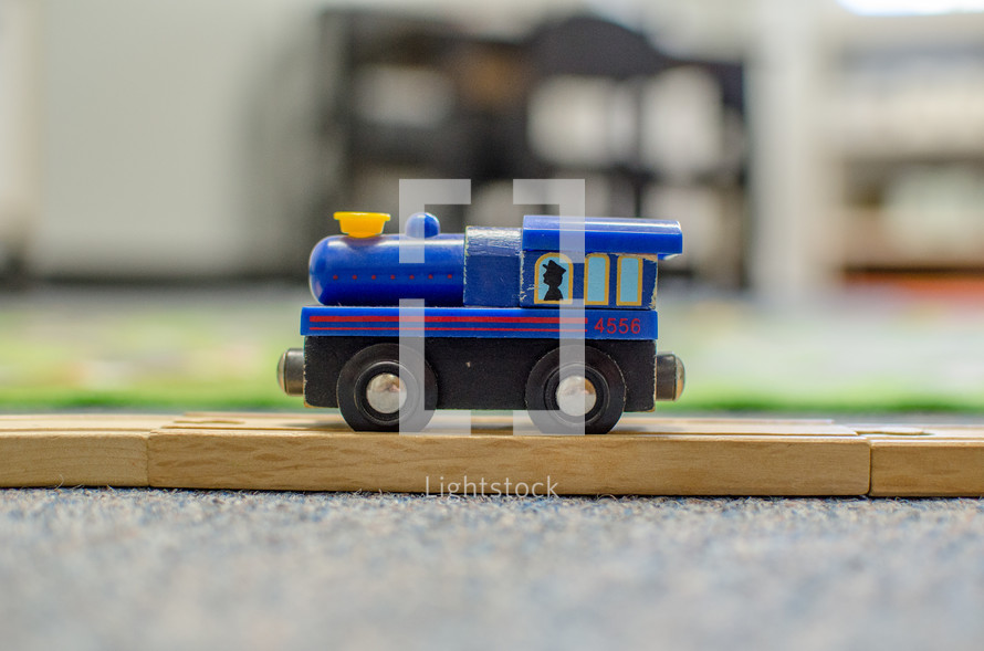 a toy train on a wooden track