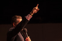 a preacher with a raised hand holding a microphone