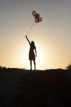 silhouette of a woman holding balloons