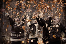 A joyful shot of youthful girls smiling and laughing as they throw the autumn leaves in the air.