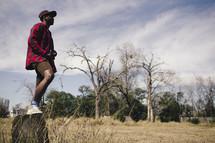 an african-american man standing on a stump outdoors
