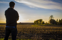 man standing in a freshly plowed field