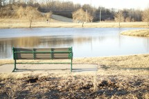 A bench overlooking a small pond.