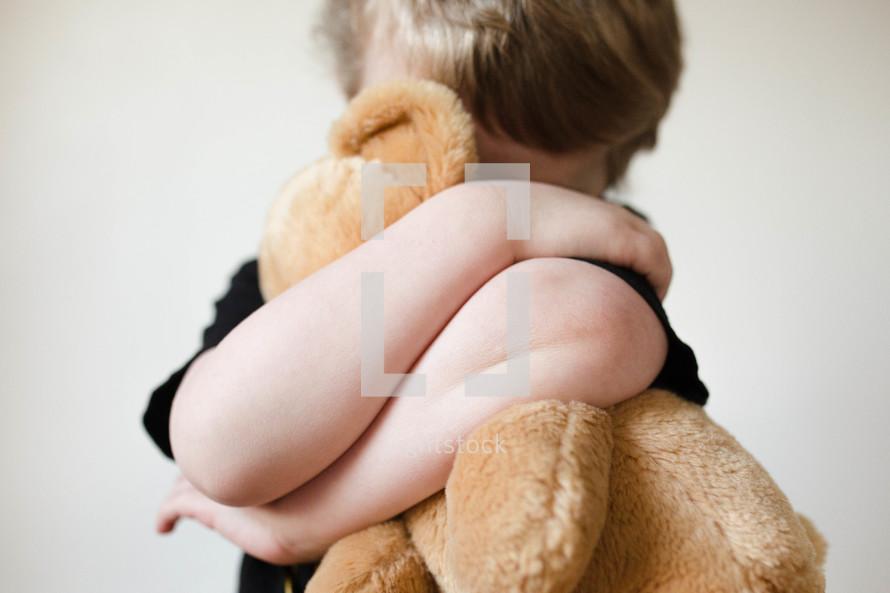child hugging a teddy bear