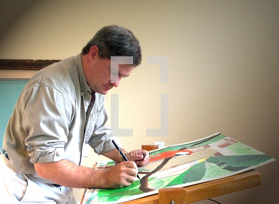 An Artist  with rolled up shirt sleeves works intently on a new painting at his easel in his art studio creating a new illustration.