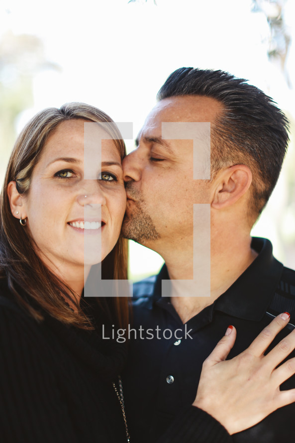 a husband kissing his wife on the cheek