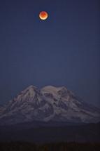 blood moon over a mountain peak