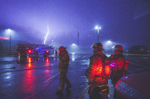 fire fighters standing outdoors and a lightning strike
