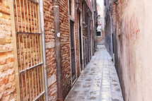 Narrow passage with pipes and bars, a back street of Venice