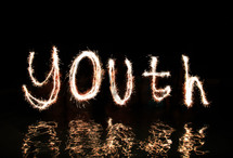 The word 'Youth' written in fireworks (by five 'artists' standing in waist high water).