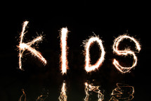 """Kids"" written in fireworks (by four 'artists' standing waist high in water)."