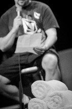 Man sitting on a stool on a stage reading notes into a microphone.