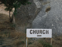sign pointing the way to a church