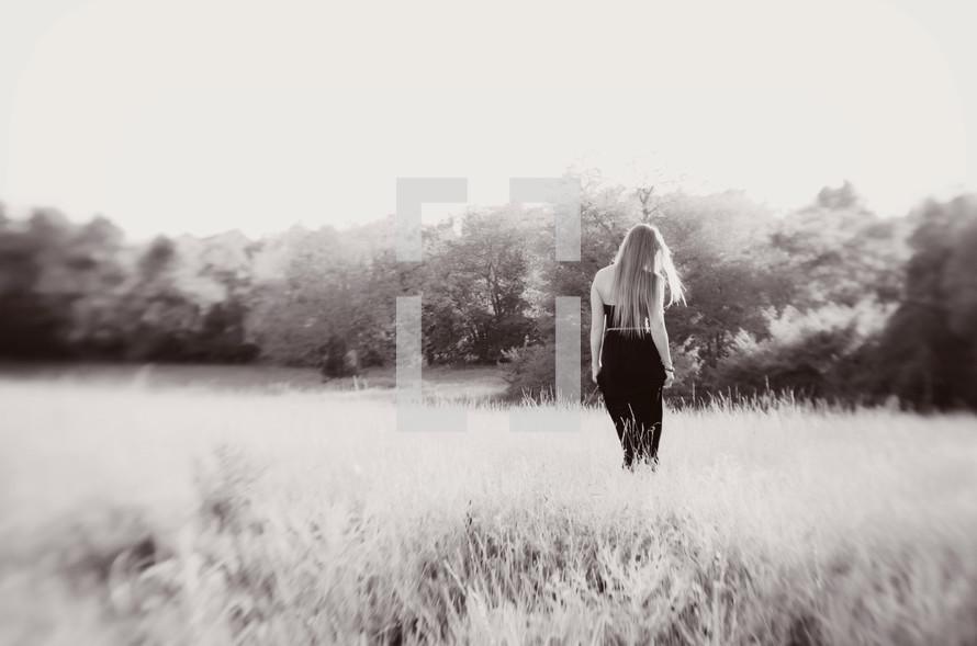 woman walking in a field in a formal dress