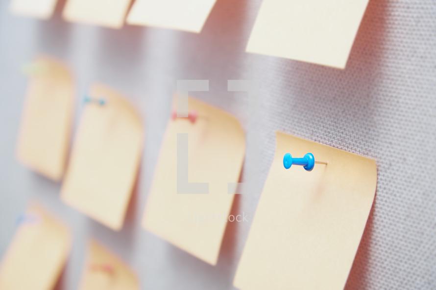 blank sticky notes on a bulletin boards
