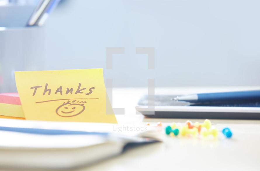 thanks on a sticky note on a desk