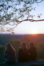 friends sitting at the edge of a cliff at sunset