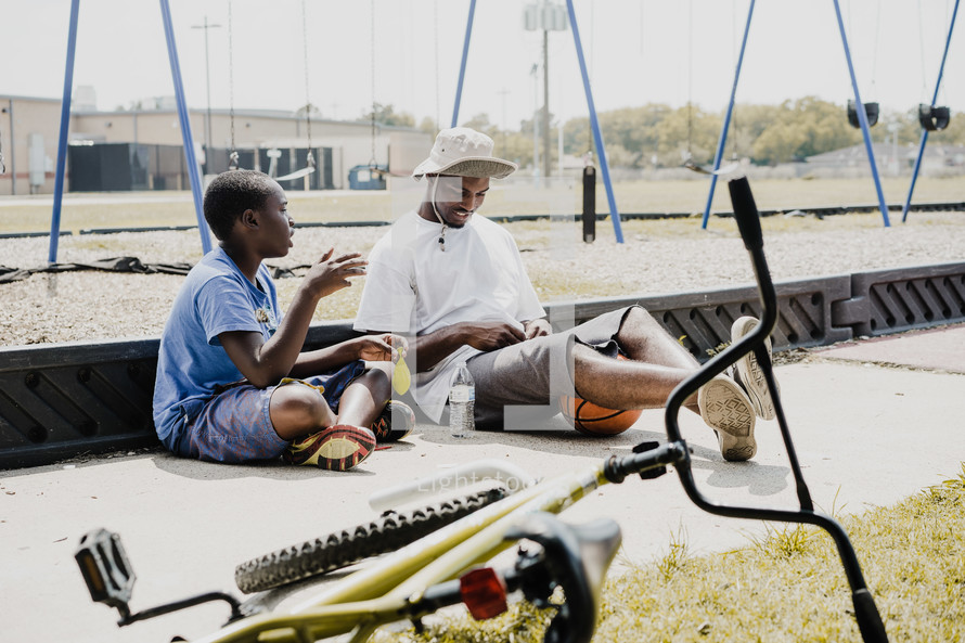 father and son sitting and in conversation in front of a playground