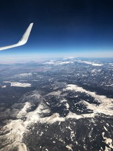 wing of a plane over mountains