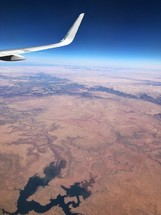 wing of a plane flying over a desert