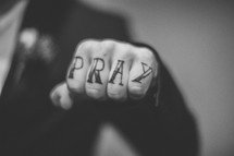 """Pray"" written on the knuckles of a man's hand."