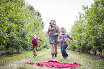siblings running in an apple orchard
