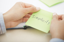 a woman holding a sticky note with the words simplicity