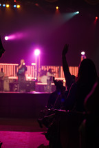 man singing on stage and an audience with raised hands