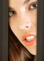 Young sexy model peeking into the door or between walls