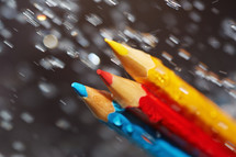 blue, yellow, Red crayon under the rain