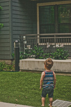 toddler boy standing outdoors in the grass