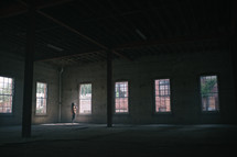 a woman standing in an empty warehouse building