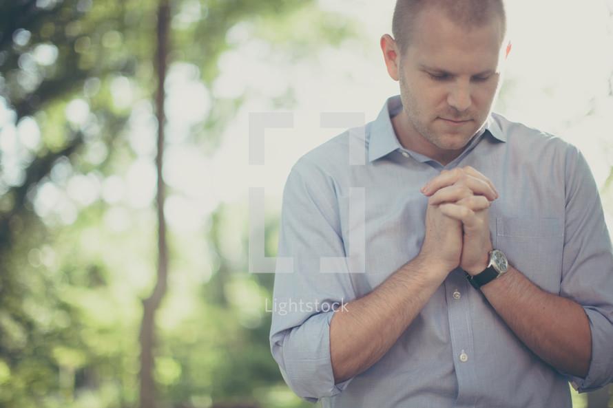 Man praying outside.