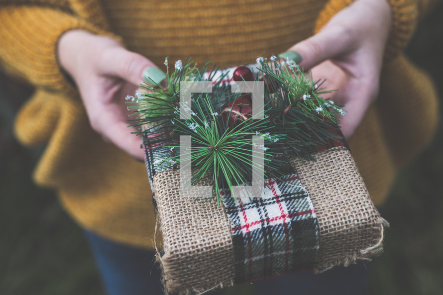 woman holding a wrapped Bible Christmas gift