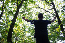 boy standing outdoors in a forest with hands raised