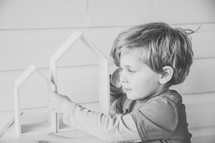 a child playing with wooden house forms