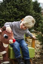 a boy child petting a stuffed Rudolph in a Christmas tree farm