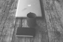 A laptop, coffee mug and notebook on a table