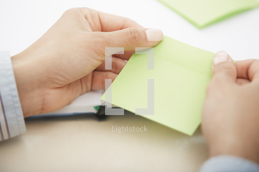 woman holding a pad of blank sticky notes