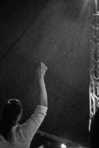 A woman with arms raised during a church service.