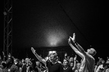 A church congregation with their hands raised during a church service.