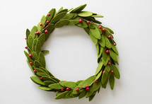 a Christmas wreath of felt green leaves and red berries on white background