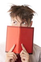 a man peeking from behind a book